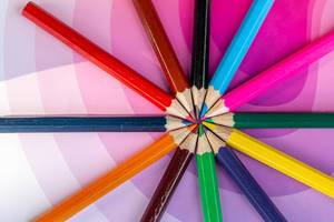 Pencils of different colors laid out on a pink background