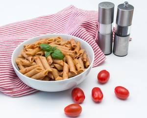 Penne mit Tomatensoße, Basilikum und frischen Tomaten mit Salz- und Pfefferstreuer