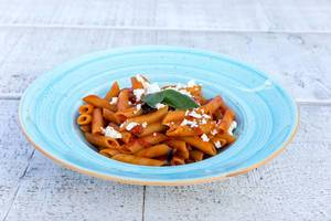 Penne pasta with tomato sauce and grated feta cheese