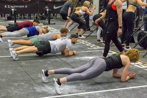 People doing a plank next to each other while others do different exercises