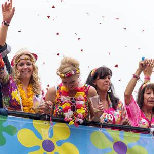 People in colorful outfits celebrating and drinking on a bus