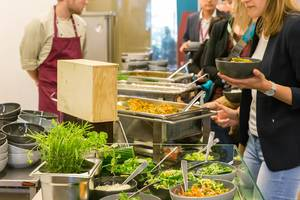People queuing for a healthy balanced lunch meal with salad bar at the buffet of AXA