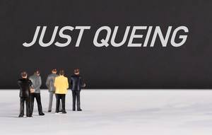 People standing in front of Just Queing text