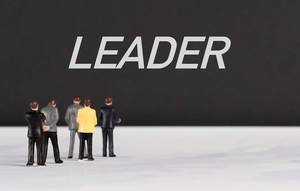 People standing in front of Leader text