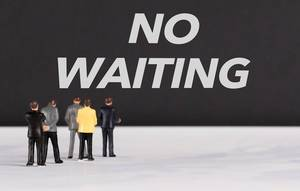 People standing in front of No Waiting text