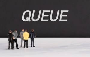 People standing in front of Queue text