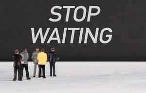 People standing in front of Stop Waiting text