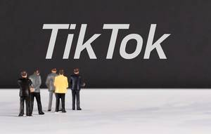 People standing in front of TikTok text