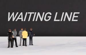 People standing in front of Waiting Line text