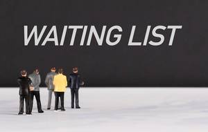 People standing in front of Waiting List text