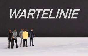 People standing in front of Wartelinie text