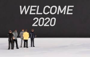 People standing in front of Welcome 2020 text