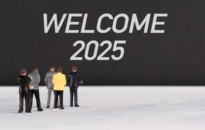 People standing in front of Welcome 2025 text