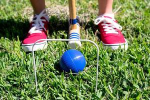 Person about to hit croquet ball