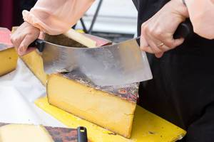 Person cutting a big piece of cheese with a large cheese knife
