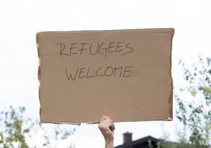 """Person hält Karton mit der Nachricht """"Refugees Welcome"""""""