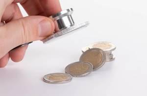Person hält Stethoskop über 2 Euro Münzen auf weißem Hintergrund