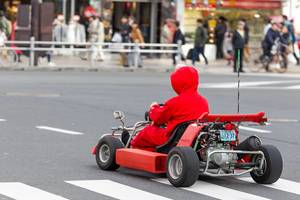 Person in Super Mario Kart Costume driving a Go Kart on the Streets of Tokyo, Japan