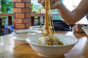 Person isst vietnamesische Nudeln mit Schweinefleisch in einem Frühstücksrestaurant in Saigon, Vietnam