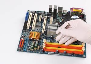 Person mit Gummihandschuhen hält einen Schraubenzieher über einer Hauptplatine eines Computers auf weißem Hintergrund
