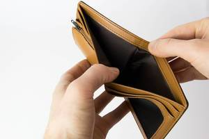 Person opening an empty wallet on white background