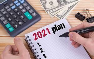 Person schreibt einen Plan für 2021 mit Filzstift in ein Notizbuch auf einem Holztisch mit Taschenrechner, Dollar Geldscheinen und Heftklammern