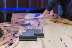 Personen fühlen Struktur eines Tisches aus Baumstamm mit auffälliger Maserung