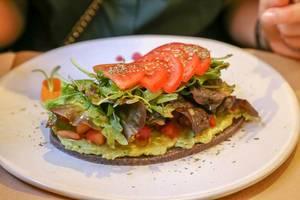 Petit Pa mit Tomaten & Avocado, Brot aus Sonnenblumen & Leinsamen, grünem Salat, Olivenöl und Oregano im Petit Brot in Barcelona, Spanien