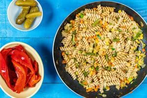 Pfanne mit gebratenen Fusilli-Nudeln mit Gemüse neben Schalen mit Essiggurken und roter Paprika auf einem blauen Holztisch Draufsicht