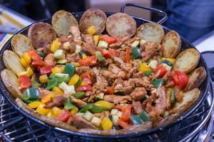 Pfanne mit Kartoffelscheiben, Fleischstücken und buntem Gemüse auf raucharmem Lotusgrill