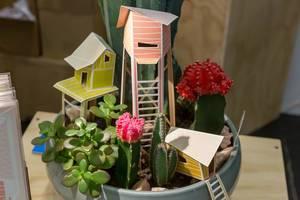 Pflanzenschale mit verschiedenen Kakteen und aus Papier gefertigten Häusern