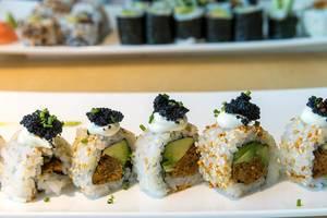 Pflanzliches Hauptgericht mit veganem Sushi, gefüllt mit Avocadoscheiben, Frühlingszwiebeln, würziger Sauce, Sesamkernen und veganem Kaviar