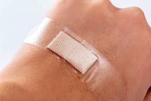 Pflaster klebt auf Hand, verhindert bluten und schützt frische Wunde vor Dreck und Bakterien