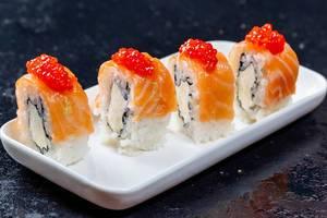 Philadelphia Sushi Rollen mit Lachs, Käse und rotem Kaviar-Topping auf weißem Teller