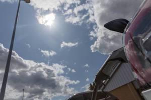 Phoenix Contact Typ 2 Stecker zum Aufladen von Sonnenenergie für Tesla Elektroautos Model 3 auf einem Aldi-Süd Parkplatz, mit Wolken vor der Sonne