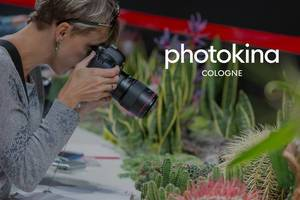 "Photography fair visitor tests camera for nature photographs, next to picture title ""photokina Cologne"""