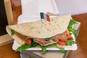 Piadina Romangola - Flatbread - with Parma ham, arugula, tomatoes, cream cheese, pesto, mozzarella and Italy flag