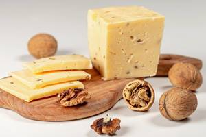 Pieces of cheese with walnuts on wooden kitchen Board (Flip 2020)