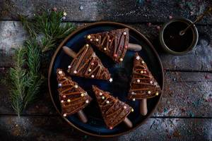 Pieces of christmas chocolate cake on a plate with tea