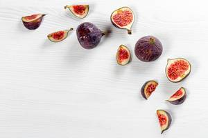 Pieces of fresh figs and whole fruit on a white wooden background with water drops (Flip 2019)
