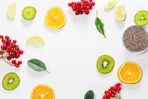 Pieces of fresh fruit, berries and green leaves with Chia seeds on a white wooden background. Top view (Flip 2019)