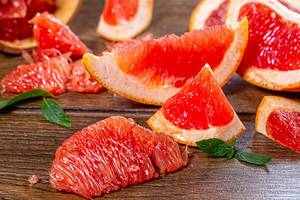 Pieces of fresh grapefruit on a brown wooden background (Flip 2019)