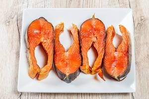 Pieces of smoked salmon on a white plate. The view from the top (Flip 2019)