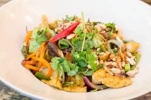 Pikantes veganes Bio-Tofu mit Zwiebeln, Pak-Choi, Champignons, Bandnudeln und Erdnüssen auf weißem Teller im Nahaufnahme