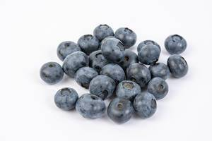 Pile of Fresh Whole Blueberries above white background (Flip 2019)