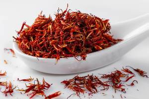 Pile of red dried saffron in ceramic spoon