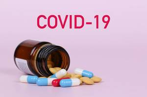 Pills poured out of bottle with COVID-19 text