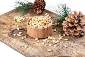 Pine nuts with pine cones and branches on an old kitchen Board (Flip 2020)