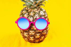 Pineapple in round sunglasses on a yellow background (Flip 2020)
