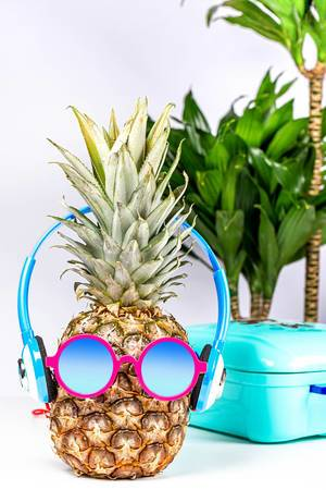 Pineapple in sunglasses and headphones with a suitcase and palm trees in the background
